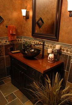 A half bath with a vessel sink mounted on a granite vanity counter by Neal's Design Remodel.