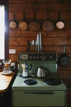 Vintage stove with sweet copper pans hanging above it