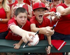 Young fans try for autographs by Los Angeles Angels first baseman Albert Pujols before a spring training baseball game against the Texas Rangers in Tempe, Ariz., Sunday, March 25, 2012. (AP Photo/Chris Carlson)
