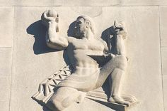 Figure representing engineering, holds aloft a dynamo and is flanked by a bridge and a road, on the Rackham Memorial Building in Detroit, Michigan, former home of the University of Michigan Extension Service and the Engineering Society of Detroit. Mr. Rackham was one of the original stockholders of the Ford Motor Company.