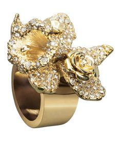 Versace. Chunky ring in gold-colored metal topped with flowers strewn with sparkly stones. Comes in a beautifully patterned case.