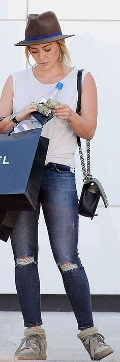 Who made  Hillary Duff's black handbag, brown handbag, blue ripped jeans, and tan sneakers