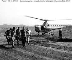 """Navy Corpsmen Herald B. Williams, James E. Carr and William N. Shipworth help carry a wounded man from a U.S. Marine Corps HO3S-1 evacuation helicopter to a hospital in Korea. Helicopter is from squadron VMO-6. Original photo is dated 3 October 1950, in which case it was probably taken during Marine Corps operations in the vicinity of Seoul, Korea. Note extensive """"Quonset"""" hut facilities in the distance."""