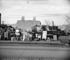 Boys standing in front of pile of appliances and junk, 320 Kirkpatrick Street, Hill District, March 1951 - Teenie Harris