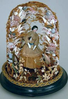 Antique China doll with shell and seaweed surround...displayed in glass dome.