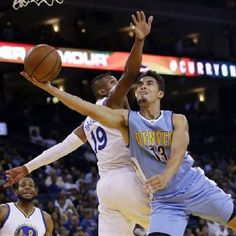 photo - Denver Nuggets' Nick Johnson (13) drives past Golden State Warriors' Leandro Barbosa (19) during the first half of an NBA preseason basketball game Tuesday, Oct. 13, 2015, in Oakland, Calif. (AP Photo/Marcio Jose Sanchez)