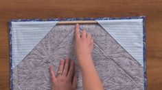 How to Hang A Quilt on a Wall- from National Quilters Circle. Free Video 5:39 Angie Hodapp demonstrates how to avoid making a sleeve by folding two square in half, baste the triangles in two corners of the quilt and add your binding. You can hang your quilt with just one hook/nail at the same time you're making your binding. VisitSite: http://www.nationalquilterscircle.com/video/hang-quilt-wall/