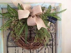 spring grapevine wreath with greenery, chalkbard sign and birds nest and a burlap bow with a touch of black chevron on Etsy, $28.00