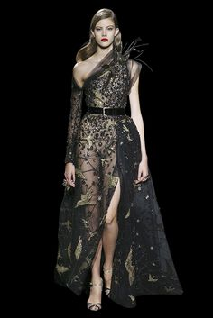 Long split dress in guipure, with an asymetric top, «Star Atlas» and birds beaded with anthic gold and black silk threads, sequins and crystals. Bird brooch set with beads, sequins, crystal stones and feathers.