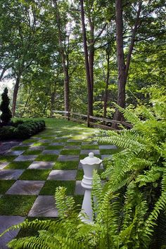 A chessboard lawn here furnished with a giant chess piece can be used to transition one area of the garden to another..