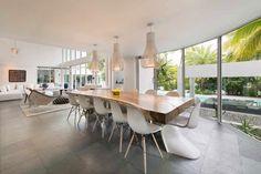 table salle à manger en bois brut et chaises Charles Eames et Panton blanches