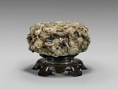 """ANTIQUE CARVED JADE BRUSHWASHER Superbly carved, heavy antique Chinese mottled cream and brown jade brushwasher; of round bulbous form, with design of dragons writhing amid swirling clouds in relief; D: 5 3/4""""; wood stand"""