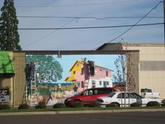 Mural being painted on the side of a store that sells used building materials to benefit Habitat for Humanity.