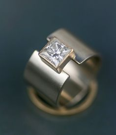 6mm genuine Charles and Colvard princess cut moissanite approx. 12mm wide brushed finish white gold band 14K yellow gold setting Also available in ...