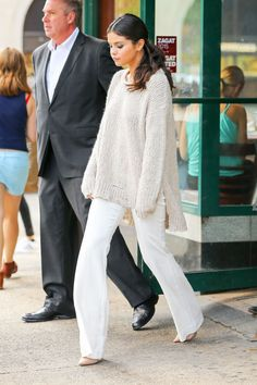 Selena Gomez wears a textured off-white sweater, crisp tailored white pants, and nude pointed toe pumps