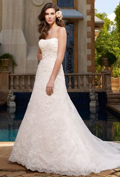 Brides: Casablanca Bridal. A lovely fit-and-flare gown, this gown has a softly scooped and ruched crystal taffeta empire bodice. The skirt is embellished with beaded lace appliqu�s and finished with a scalloped hem.