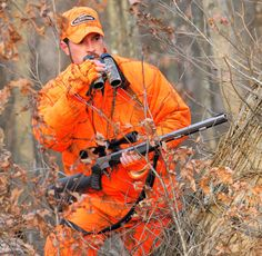 One of the Realtree camo patterns in action: A hunter wearing Realtree AP ™ Blaze orange camo in the woods rests his firearm on one thigh as he raises his binoculars to his face.