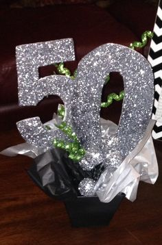 Sparkly silver 50th birthday party centerpiece. Follow us for more planning inspiration or contact us at www.tidesevents.co.uk for help planning your party.