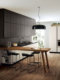 Jasper Morrison's Smithfield pendant light complements the neutral color palette and wood tones in this minimalist kitchen.