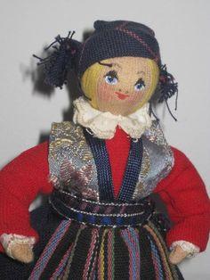 En liten Charlotte Weibull docka, gumma med folkdräkt på träställning på