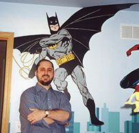 Artist Tom Perkowitz poses with one of his murals.