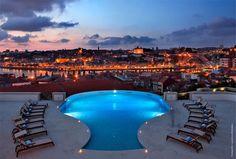 """Distrito do Porto tem uma das piscinas mais espetaculares do mundo.  A piscina exterior do hotel The Yeatman, em Vila Nova de Gaia, é uma das mais espetaculares do mundo. A opinião é do jornal britânico The Telegraph, que reuniu sete exemplos de piscinas espalhadas pelo globo que são """"muito mais do que simples lugares para nadar"""". A piscina situa-se no telhado do hotel..."""