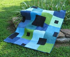 "Altered Version of the City Park Quilt Pattern put out by Cherry House Quilts. (I down sized the number of blocks needed to create it in a crib size.)  Finished size is 36""w x 45""l  Kona Cotton Solids I used: Black - Peacock - Alpine - Bahama Blue - Lime - Windsor - Pistachio -Delft - Turquoise (backing and binding was done with hand dyed fabric). It was machine quilted with a walking foot on my 1940's Singer 201-2 using (Superior Threads) King Tut Variegated Thread in color 935 Arabian…"