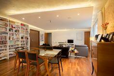 Sala de estar. Parede de tijolinhos originais descascados, piso de madeira, forro de gesso com spots e sanca com fita LED, cimento queimado no teto.