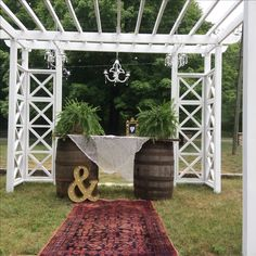 vintage wedding ceremony arbor decorations with wine barrels, old door, ferns, lace and candle chandeliers.
