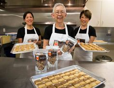 Tule Yomogida, center, shows packages of the alfalfa honey granola her company, Tule's Cookies, makes. Her daughter Jennifer Szostak, left, and sister Laura Katayama assist in the business. Szostak holds cranberry almond thins; in the foreground are Hawaiian tiles.