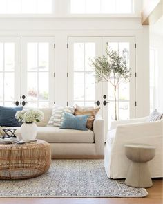 bright white cozy living room natural light French doors while sofa white armchair wicker coffee table frenchDecorating bright white cozy living room natural light French doors while sofa white armchair wicker coffee nbsp hellip white Living Room White Armchair, Wicker Coffee Table, Interior Minimalista, Coastal Living Rooms, White Living Rooms, Natural Living Rooms, Bright Living Room Decor, White Family Rooms, Hamptons Living Room