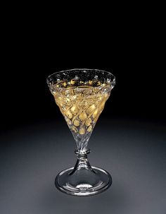 Corning Museum of Glass -- Venice 1550-1600 -- PRIMARY DESCRIPTION  Goblet. Colorless, with grayish tinge; very bubbly, few impurities. Applied, gilded. Mold-blown conical bowl is joined by single merese to infolded pedestal foot with pontil mark. Mold-blown design of leaf and tendril pattern. Below rim, frieze of wavy lines flanked by dotted and solid lines, all heightened by gilding. Glass contains bubbles and inclusions.