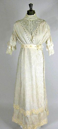 Day dress, ca.1912. Ivory silk with narrow figured gray stripe. Crossover bodice has gilt metal button detailing, guimp and undersleeves are of ivory lace, and tunic skirt is edged with coarse appliquéd cream lace. Brightwells