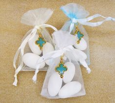 The favors are made of:  - CCB clover / cross bead in blue and gold (a CCB bead is a copper coated acrylic bead) - Organza Pouch in blue or white or ivory - three (3) white Jordan almonds  Ready for use.  Personalization and customization available on this item.
