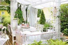 Tee omakotitalon pihalle maalaisromanttinen terassi helposti. Valokatteen alla tekstiilit ja vanhat huonekalut pysyvät suojassa.  Lue helpot vinkit!
