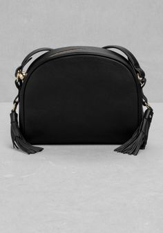 & OTHER STORIES An endearing small leather bag embellished with prominent tassels on each side. Featuring a long shoulder strap that enables the bag to be carried crossbody.