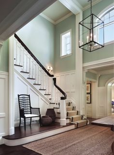 Stairwell entry into foyer, black and white, thick trim, wainscoting