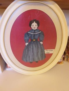 antique china head doll needlework in old oval frame
