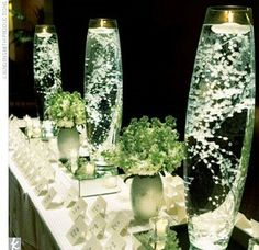 Baby's breath under water with waterproof led light on bottom.  Lori: I don't know that I want them this tall. Maybe like half this size. I love the submerged babies breath. I don't like the little bush center pieces in this pic.
