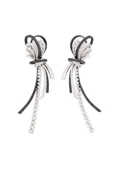 Chanel Couture earrings in 18K white gold, set with 274 round-cut white diamonds, 16 baguette-cut white diamonds, and 236 brilliant-cut black diamonds.