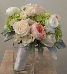 Bride bouquet with green hydrangea, white roses, peach garden roses, white ranunculus, and dusty miller.