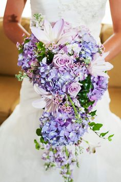 BEAUTIFUL Cascading Bridal Bouquet Which Is Arranged With: Purple Jumbo Hydrangea, Pastel Lavender Lilies, Lavender Roses, White Stock, Pink Wax Flower, & Several Varieties Of Lovely Green Foliage××××