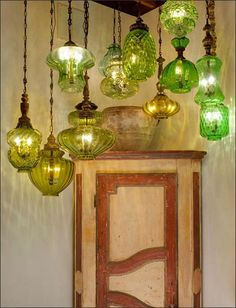 Painted Italian corner armoire (one of a pair) lit by a group of hanging vintage lanterns.  Photo by Peter Vitale