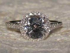 A beautiful and delicate engagement ring featuring a pastel gray sapphire in white gold diamond halo.  The center stone is a beautiful round Ceylon sapphire, which weighs 2.2 carats and measures 7.5 mm diameter. It is a nicely cut and basic heat only. The color is pretty much a pure medium gray, a pretty rare color for sapphire. The sapphire is eye-clean, and has some very small specs that may be visible at very close view and pretty much get lost in the sparkle. This one doesnt photograph…