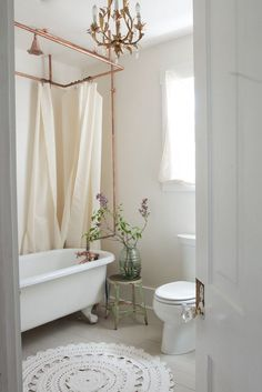 French style bathroom with a freestanding bathtub, copper pipes, gold chandelier, and crochet floor mat.
