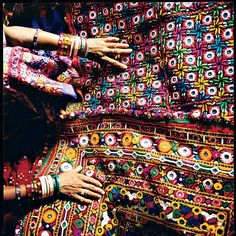 "Near Hodka, India, Virabal Achaar Harijan displays her family's embroidery. The stitchwork is called paako, or ""solid,"" and often includes small mirrors."