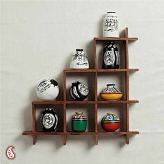 Wall Decor With Miniature Pots - A modern yet traditional wall decor design of miniature painted pots will surely enhance the look of your walls or showcases.This wooden mount is delicately placed with beautiful miniature terracota vases handpainted in multicolours with madhubani and worli styles.  http://www.indiaplaza.com/wall-decor-with-miniature-pots-handicrafts-han15032012apr214-10.htm?utm_medium=social-media_campaign=Pinterest+daily+updates_source=Pinterest