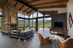 luv the stone on fireplace.really like contrast of the large header beam, like windows.Elegant mountain contemporary home in Colorado radiates with warmth