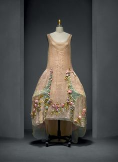 Boué Soeurs (French, active 1899–1957). Court Presentation Ensemble, 1928, Haute Couture. Hand–sewn ivory silk tulle, machine–embroidered with couched silver cord in a foliate and vermicelli pattern; insets of silver–blue silk and metal lamé with machine–picot edging; hand–appliquéd with hand–embroidered white silk tulle with artificial flowers in pink, purple, green, yellow, and blue silk ribbon and floss. Photo © Nicholas Alan Cope. #ManusxMachina #CostumeInstitute
