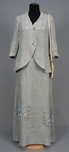 Circa 1918 pale blue linen summer walking suit and handbag:  jacket with self button and elbow length sleeve, trimmed with cotton, lace and lace covered buttons, matching A-line skirt with lace bands at sides of lower skirt. Together with a cotton lace purse.